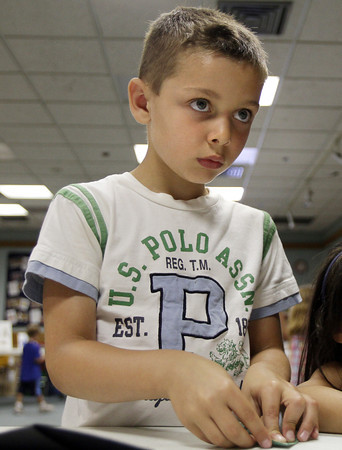 David Le/Gloucester Daily Times. Frankie Desisto, 6, concentrates on a board with directions on how to make an origami hat during Origami Around the World held at the Gloucester Lyceum and Sawyer Free Library on Monday morning. 7/11/11.