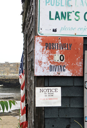 "David Le/Gloucester Daily Times. A rain-soaked, slightly tattered American flag hangs forlornly on the side of Mourey's Shack, one of the last fish shacks in Lane's Cove, near a notice from the city, warning that the building is ""Unsafe and Dangerous."" City Councilors are working with the mayor to restore this historic landmark in Lanesville. 7/13/11."