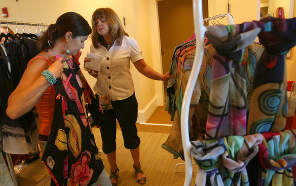 Peggy Russell of the Pop Gallery in Gloucester shows one of her designs to Jane Brown of Groveland during the Barefoot at Rockport Designer Pup Up Shops at the Shalin Liu Reception Hall yesterday. Photo by Kate Glass/Gloucester Daily Times
