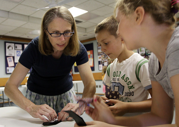 David Le/Gloucester Daily Times. Laura Geggis, left, shows Frankie, 6, and Serene Desisto, 8, how to make an origami fold at Origami Around the World at Gloucester Lyceum and Sawyer Free Library on Monday morning.7/11/11.