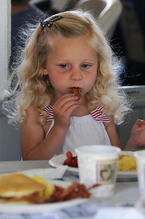 Manchester:  Abby Kent 2, takes a bite of her bacon at the Annual Red White and Blue Breakfast in Manchester Tuck's Point Saturday morning.Proceeds benefit Rotary Club scholarships and community service projects. Desi Smith/Gloucester Daily Times. July 2,2011.