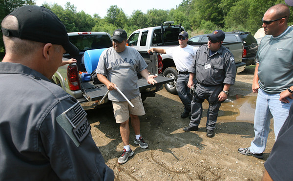 "Gloucester Police Sgt. William Leanos draws a rough map in the dirt as he organizes members of the Cape Ann Regional Response Team in the search for Sergei ""Jay"" Samoylenko, who was reported missing late Monday night. His body was found at Haskell Pond Tuesday afternoon. Photo by Kate Glass/Gloucester Daily Times"