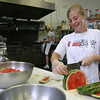 Ashley Geary jokes with Charlene Morrison, rear, while preparing a watermelon salad at Classic Cooks in Gloucester. The business was forced to throw away most of their refrigerated and frozen food due to the power outage at the Blackburn Industrial Park, which lasted into the weekend. Photo by Kate Glass/Gloucester Daily Times