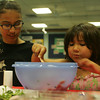 Clara Mazo, 10 helps Olivia Hogan-Lopez 7, both from Gloucester, mix together the tomatoes and dressing for the bruschetta they were making during the Cooking Around the World event at the Sawyer Free Library in Gloucester. Photo by Maria Uminski/Gloucester Daily Times