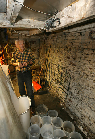 Jack Carter of the Raymond Alger gallery on Pleasant Street in Gloucester looks up at spots in the ceiling where water leaks into his basement. A fire in March gutted the building adjacent to the gallery and water leaks through the building into the basement. Photo by Kate Glass/Gloucester Daily Times