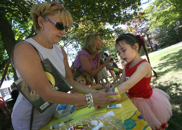 Cynthia Calabrese helps Grace Kelly, 5, put on a Wonder Woman bracelet during a Super Heroes Tea Party at the Manchester Library on Wednesday. Grace, who is from Ireland, is in town visiting family. Photo by Kate Glass/Gloucester Daily Times