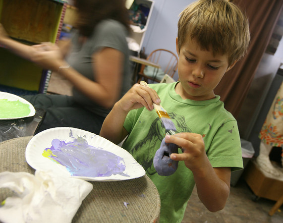 Alex Krupka paints a ceramic whistle during a painted furniture class at the Rockport Art Association yesterday morning. Krupka had finished painting his treasure chest and went to another project. Photo by Kate Gass/Gloucester Daily Times