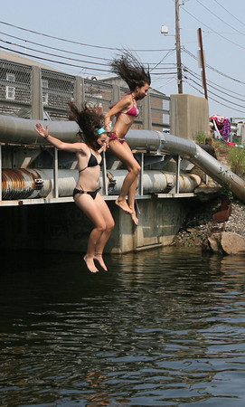 Anna Heffernan, left, of Essex and Kenna O'Maley of Gloucester hold hands as they jump off the Causeway Tuesday afternoon. Photo by Kate Glass/Gloucester Daily Times