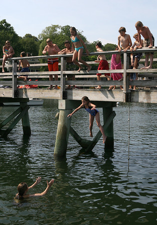 Abby Giaconia's friends cheer her on as she jumps off the foot bridge in Annisquam for the first time yesterday afternoon. It took Abby a while to muster up the courage, but she said it was fun and that she would probably do it again. Photo by Kate Glass/Gloucester Daily Times