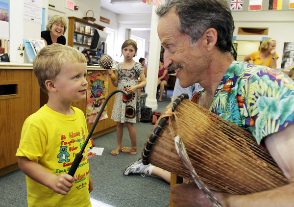 David Le/Gloucester Daily Times. Doron Appleyard, 3, of Essex, uses a mallet to bang on a drum held by guest musician John Root at A World of Music program held at the TOHP Burnham Library in Essex on Monday afternoon. 7/11/11.