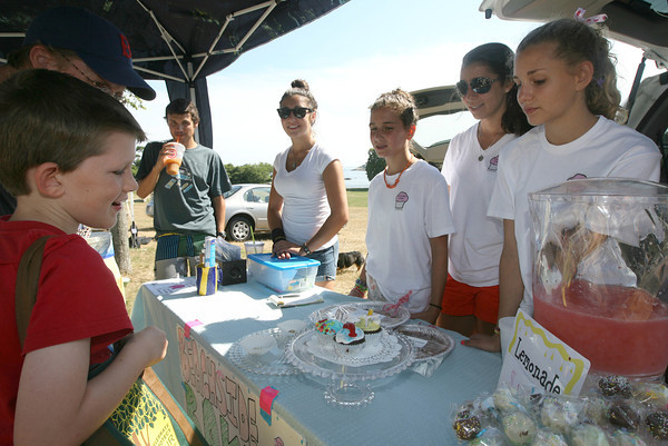 Stephen Donlon checks out the display of cupcakes made by the Beachside Bakers at the Cape Ann Farmers Market yesterday afternoon. The cupcakes are made by Jessica Adam, Audrey Adam, Sara Adam, Rene Firman, and Caitlin Coates (not shown). The girls sell their cupcakes at the Cape Ann Art Haven booth during the market and also bake for parties. Photo by Kate Glass/Gloucester Daily Times