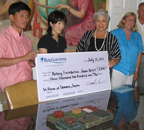 Carole Sharoff and Mayor Carolyn Kirk present a check for $3,200 from the Gloucester Rotary Club to a group of students and their chaperones visiting from Gloucester's sister city of Tamano, Japan. The money will go toward tsunami relief. Photo by Richard Gaines/Gloucester Daily Times