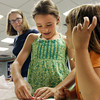 David Le/Gloucester Daily Times. Lila Olson, 9, smiles as she folds an origami Eiffel Tower while talking with Lotus Marsh, 5 right at Origami Around the World held at Gloucester Lyceum and Sawyer Free Library on Monday morning. 7/11/11.