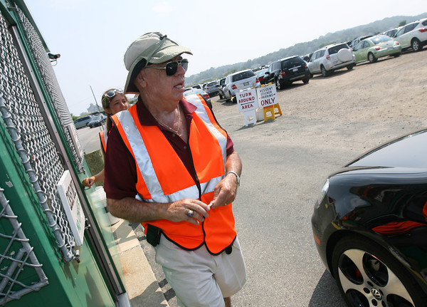 John Quinn wears a hat to keep out of the sun to stay cool while working at the Good Harbor Beach parking lot yesterday. Photo by Kate Glass/Gloucester Daily Times