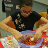 Clara Mazo, 10, of Gloucester, puts the finishing touches on her bruschetta  during the Cooking Around the World class at the Sawyer Free Library in Gloucester. Photo by Maria Uminski/Gloucester Daily Times