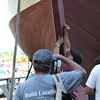 Essex:  Some of the boat builders mark the bow of the Ardelle along with their name, to see who comes the closest to where the water line will end up, thats with out the mast and other pieces that will complete the Ardelle just before the launch into the Essex River Saturday afternoon at H.A Burnham. Desi Smith/Gloucester Daily Times. July 9,2011