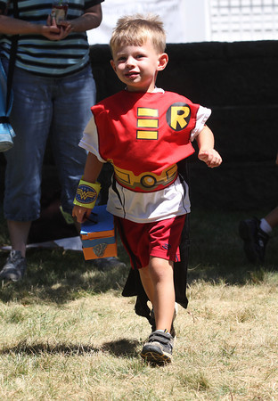 Carson Croft, 4, of Manchester participates in the lunchbox relay during a Super Heroes Tea Party at the Manchester Library yesterday morning. Carson dressed as Robin while his twin brother, Jarrett, dressed as Batman. Photo by Kate Glass/Gloucester Daily Times