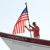 Essex: Steve Willard of Marblehead who helped on the build, places the american flag at the stern of the Ardelle just before the launch into the Essex River Saturday afternoon at H.A Burnham. Desi Smith/Gloucester Daily Times. July 9,2011