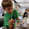 David Le/Gloucester Daily Times. Alex Krukpa, 5, of Lexington carefully paints his decorative art board at Rockport Art Association's Garden Sculpture workshop. 7/12/11.