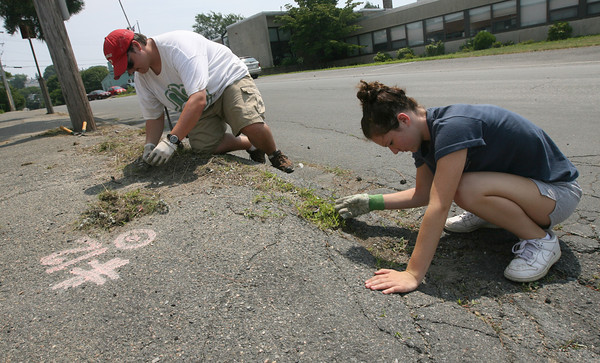 Abram Buckner of North Carolina and Lindsey Rose of New Hampshire weed the sidewalk next to Pathways for Children. The two are attending Passport Camp, which does volunteer work all around the country for eight weeks. In addition to landscaping around Pathways, the campers also helped repaint The Open Door. Photo by Kate Glass/Gloucester Daily Times