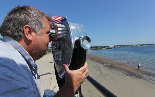ALLEGRA BOVERMAN/Staff photo. Gloucester Daily Times. Gloucester: Matt Hady of Gloucester looks out at Ten Pound Island and was able to also see a glimpse of Cape Cod, with a long range viewer along Stacy Boulevard on Monday afternoon.