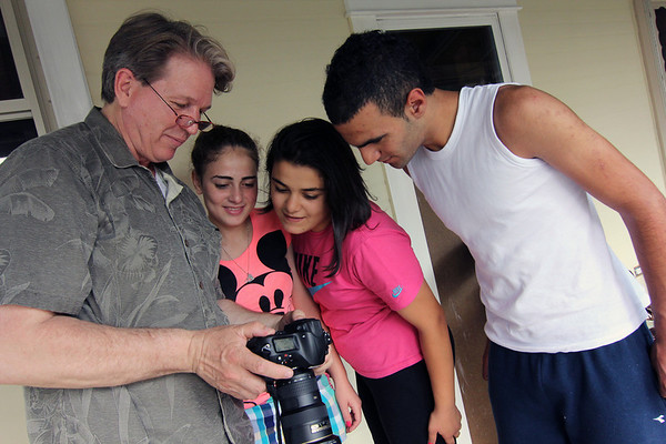 Allegra Boverman/Staff photographer. Gloucester Daily Times. Gloucester: Tom Baker, left, has been taking photos of the Israeli students visiting and staying at his home. From center are Meramar Abuleil, Malak Habib-Allah, and Kenan Shihadi, all 16.