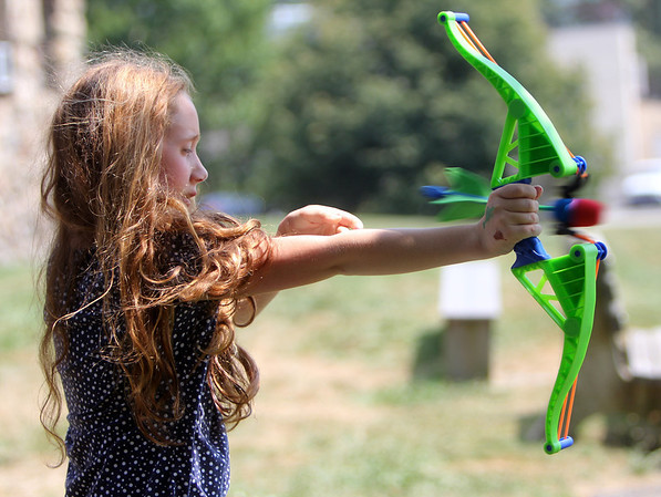 """ALLEGRA BOVERMAN/Staff photo. Gloucester Daily Times. Essex:  Eden Mayer, 9, practices archery during the Wild West Fest at the Essex Library on Tuesday. There were many western-themed activities and crafts including making sheriff's badges out of cookies, lasso the cowboy boots, archery and pony rides. Special foods included """"cactus"""" punch, beef jerky, trail mix and biscuits and jam."""