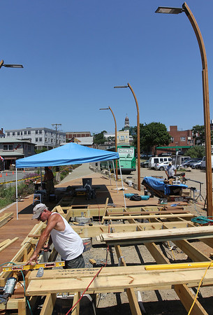 ALLEGRA BOVERMAN/Staff photo. Gloucester Daily Times. Gloucester: The Harborwalk area at the I-4, C-2 site is still under construction. A boardwalk with a built-in ramp is being built there. Dave Mason, lower left, works on Thursday.