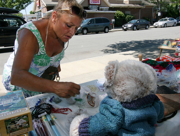 ALLEGRA BOVERMAN/Staff photo. Gloucester Daily Times. Gloucester: Mary Meofotistos of Gloucester browses among the jewelry for sale at the Christmas in July fundraiser outside the center on Friday morning. There were raffles and bargains to help support the group.