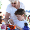 Maureen Wilkinson of South Portland, Maine assists her grandson, four-year-old Wyatt Wilkinson of Rockport, with an arts and crafts project at the Cape Ann Farmer's Market on Thursday. Photo by Maria Uminski/Gloucester Daily Times