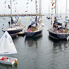 Marjorie Nesin/Staff photographer. Gloucester Daily Times. Rockport:A group of 8 and 9-year-olds, in their third week of sailing at Sandy Bay Yacht Club, sail by the moored Naval Academy boats after they arrived in Rockport on Friday morning for the weekend.