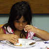 6-year-old Alycia Hogan-Lopez of Gloucester meticulously constructs her s'more at the Cooking Club's Midnight Snacks cooking event at the Sawyer Free Library in Gloucester. Photo by Maria Uminski/Gloucester Daily Times