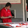 ALLEGRA BOVERMAN/Staff photo. Gloucester Daily Times. Essex: Michael Webber of Gloucester works a sudoku puzzle while working at Woodman's in Essex on Friday afternoon at the outdoor lobster stand. He's worked there for four years and will be attending University of Delaware in the fall.