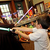 "ALLEGRA BOVERMAN/Staff photo. Gloucester Daily Times. Manchester: Atticus Smith, 5, right, duels with Jedi Master Jim at Manchester Public Library on Monday during a ""Jedi Knights in Training"" workshop. Participants took part in various challenges, including a ""Jedi Force Magic Show,"" where they ""used the force"" to change a balloon into a giant star flower. They also participated in a ""laser balloon barrage"" where Jedi Master Jim would fire long, skinny balloons at the children and they had to catch and fire them back at him."