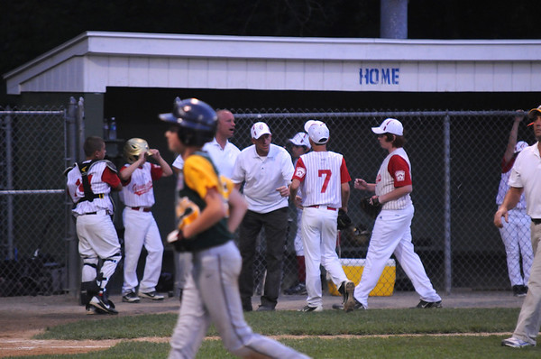 Beverly:  Gloucester players and coaches congratulate pitcher Eric Chalmers after a good inning during their game against Manchester at Harry Ball Field in Beverly. Jim Vaiknoras/staff photo