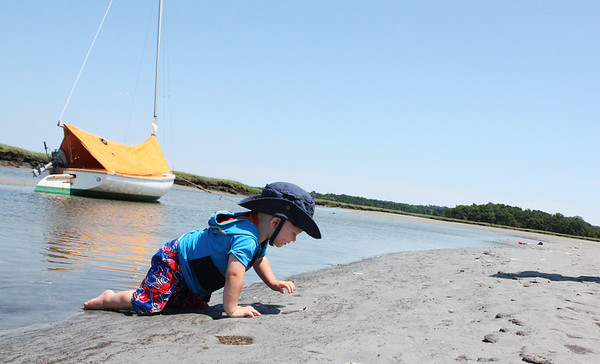 One-year-old Vaughn Creeden of Essex crawls threw the water at Comono Point in Essex. Photo by Maria Uminski/Gloucester Daily Times