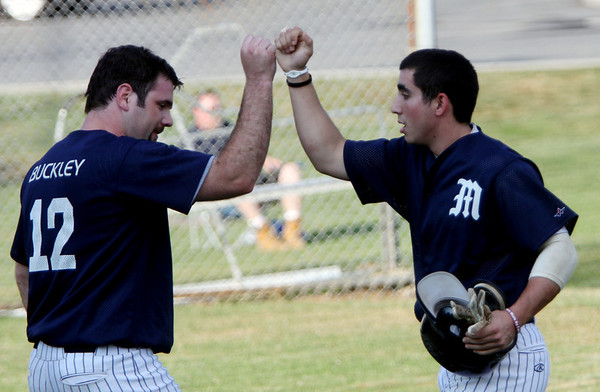ALLEGRA BOVERMAN/Staff photo. Gloucester Daily Times. Essex: Manchester's Caulin Rogers, right, is congratulated by teammate Ian Buckly after Rogers scored a run during an ITL game held against Rowley in Essex on Tuesday evening.