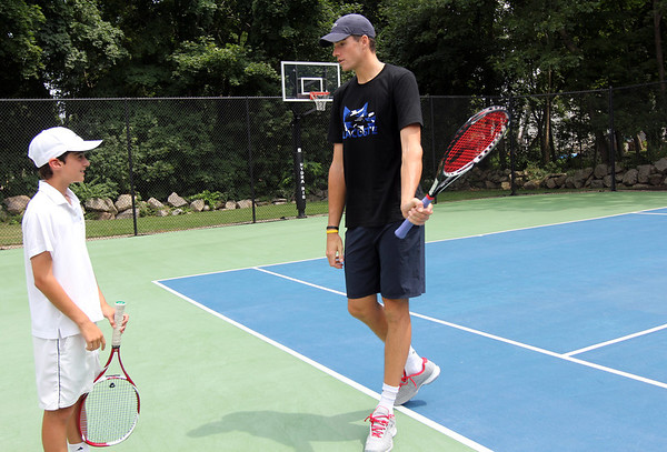 ALLEGRA BOVERMAN/Staff photo. Gloucester Daily Times. Rockport: Sam Girian, left, 13, of Manchester, discussing how professional tennis player John Isner warms up before matches during a visit Isner made to a home in Rockport on Monday. Isner will be in the Olympics in London and was to leave for there Monday night after playing with the Boston Lobsters on Monday evening at Ferncroft Country Club against the Philadelphia Freedoms.