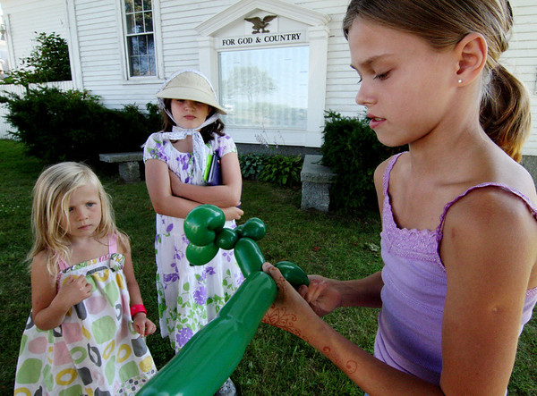 "ALLEGRA BOVERMAN/Staff photo. Gloucester Daily Times. Rockport: Alina Lorigan, 10, right, of Jupiter, Fla. who visits Rockport every summer, twists balloons into dog and other shapes for Cayla O'Sullivan-Place, 4, and Cora Johnson, 10, both of Rockport. They had all been participating in Jungle Jim's Balloons, an event held by the Friends of the Rockport Library on Tuesday afternoon at the Legion Bandstand area on Beach Street. The program was part of the ""Dream Big - Read"" summer reading program. Jungle Jim played balloon games  performed magic tricks and told stories."
