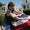 ALLEGRA BOVERMAN/Staff photo. Gloucester Daily Times. Gloucester: Everett Francis of Gloucester helps his friend Sheila Brennan to decorate her house on Centennial Avenue on Tuesday for the Fishtown Horribles Parade and July 4.