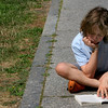 ALLEGRA BOVERMAN/Staff photo. Gloucester Daily Times. Manchester: Ellis Provost, 9, was reading a book in the sun on the front walk at Manchester Public Library on Monday afternoon.