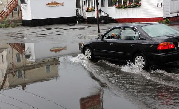 ALLEGRA BOVERMAN/Staff photo. Gloucester Daily Times. Gloucester: A car slowly makes its way up a flooded portion of Pearl Street during a sudden rainstorm on Tuesday afternoon.