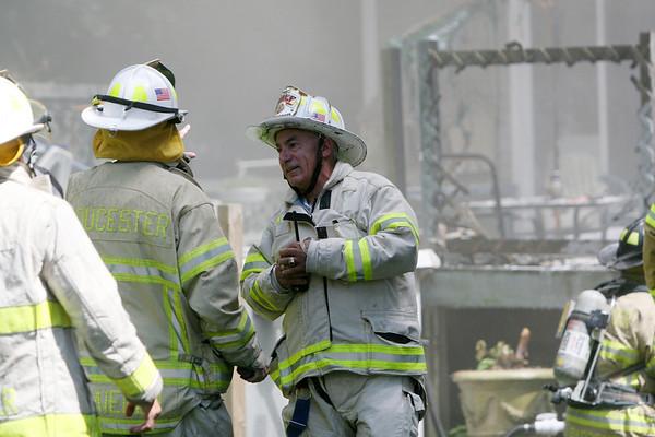 ALLEGRA BOVERMAN/Staff photo. Gloucester Daily Times. Gloucester: Acting Fire Chief Robert A. DiPoli, right, confers with firefighters at the scene of a fire at 2 Ashland Place in Monday afternoon in Gloucester.