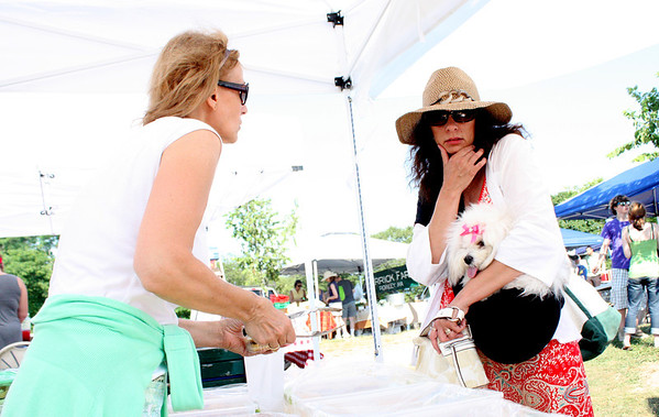 Tatiana Vazza, of Tatiana's Treats, assists Diane of Gloucester, accompanied by her dog Lola, pick out a sweet treat at the Cape Ann Farmer's Market on Thursday. Photo by Maria Uminski/Glocuester Daily Times