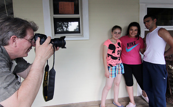 Allegra Boverman/Staff photographer. Gloucester Daily Times. Gloucester: Tom Baker, left, has been taking photos of the Israeli students visiting and staying at his home. From center, left are: Meramar Abuleil,  Malak Habib-Allah, and Kenan Shihadi, all 16.