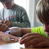 "Andrew Torri, 8 of Gloucester, puts the finishing touches on his ""Puff Car"", at the Eastern Point Day School Summer Adventures before the races begin for the Mad Scientists Exploration in Science event. The participants could only use straws, one piece of paper, four Lifesavers and two paper clips. Photo by Maria Uminski/Gloucester Daily Times"