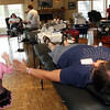 ALLEGRA BOVERMAN/Staff photo. Gloucester Daily Times. Gloucester: Christine Hammond, lying down, was giving blood during a Red Cross blood drive on Thursday in honor of her granddaughter Caleigh Harrison, who would have turned three on Friday. At left, giving her a high five, is her other granddaughter, Lizzie Harrison, 5, Caleigh's older sister. Collections specialist Sydney Fitzgerald is assisting Hammond at right.