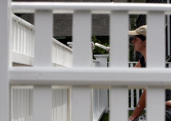 ALLEGRA BOVERMAN/Staff photo. Gloucester Daily Times. Gloucester: Katherine Dench of Gloucester paints the fence around a home in East Gloucester on East Main Street where she does general maintenance on Tuesday.