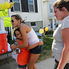 ALLEGRA BOVERMAN/Staff photo. Gloucester Daily Times. Gloucester: Bailee Militello, 6, left, of 29 East Main Street, gets a big hug from Sabrina Cardone, 17, and her mother, Laura Cardone, right, who lost their home in a fire on Monday at 2 Ashland Place. They came to say thank you to her and her family for holding a lemonade sale to raise money for them. The lemonade stand will also be open on Thursday from 2:30 - 4:30 p.m.