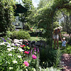 ALLEGRA BOVERMAN/Staff photo. Gloucester Daily Times.Rockport: Carol Delaney of 6 Norwood Avenue in Rockport takes her grandson Logan Fay, 10 months old, of Reading, through her garden on Thursday. Her gardens are on the Coastal Gardens tour on Friday and Satuday in Rockport.